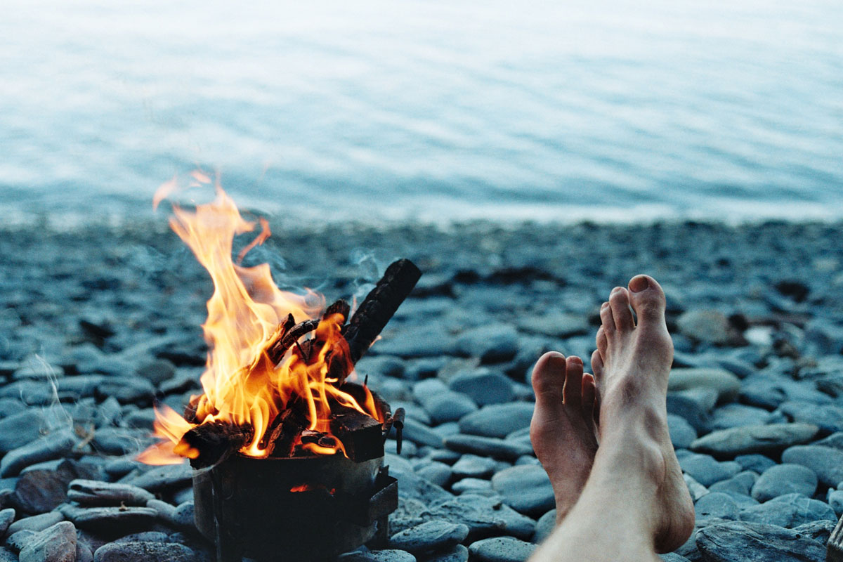 beach camp fire next to bare feet