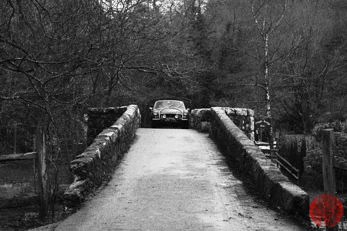 vintage mg driving over fingle bridge on dartmoor