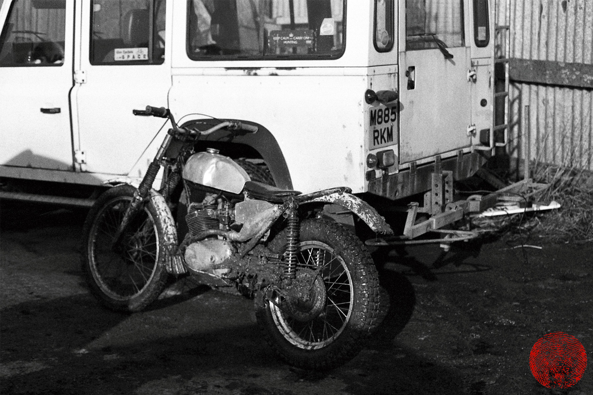 vintage custom trials motorbike leaning against land rover 110 defender