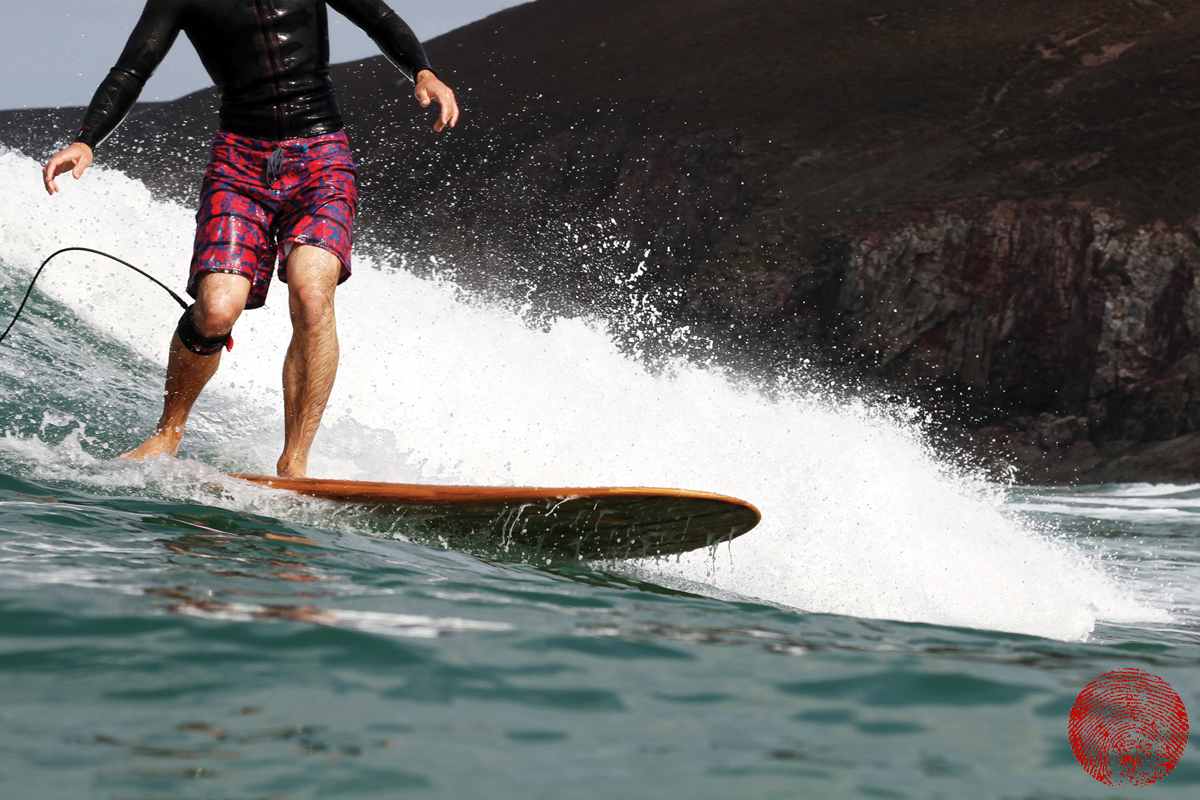 surfer wearing riz boardshorts surfing on a wooden surfboard
