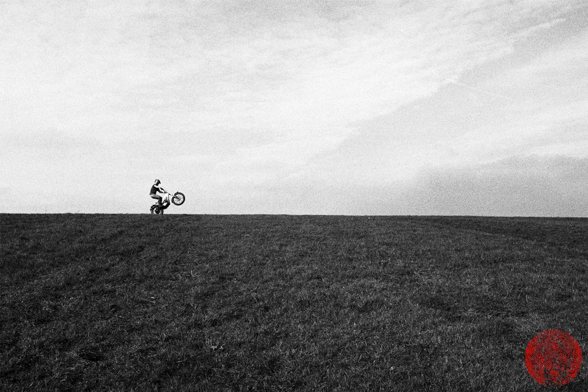 motorcyclist doing a wheelie along a ridge on a vintage yamaha ty175