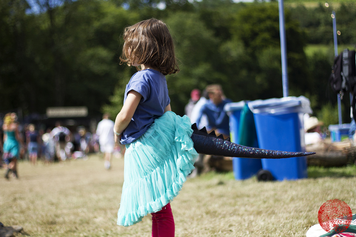 child wearing a monster tail at somersault festival 2015