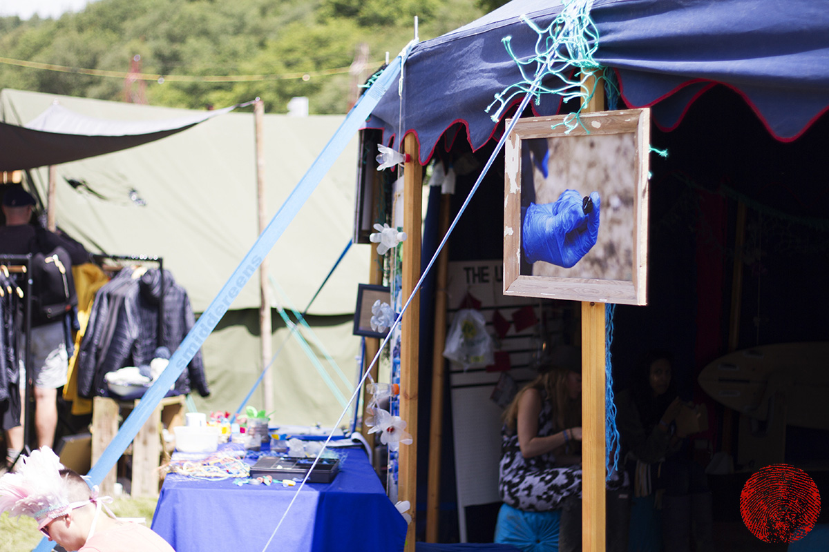 a marine plastic pollution photograph by mat arney showing plsatic stuck in a beech nut on display at the surfers against sewage tent at somersault festival 2015