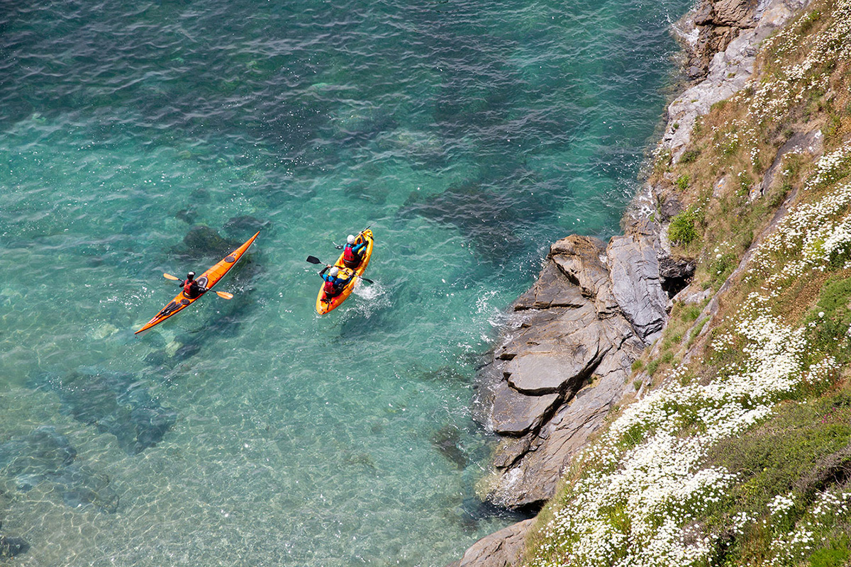 birds-eye view of two sea kayakers paddling across crystal clear turquoise waters on a trip with cornish rock tors