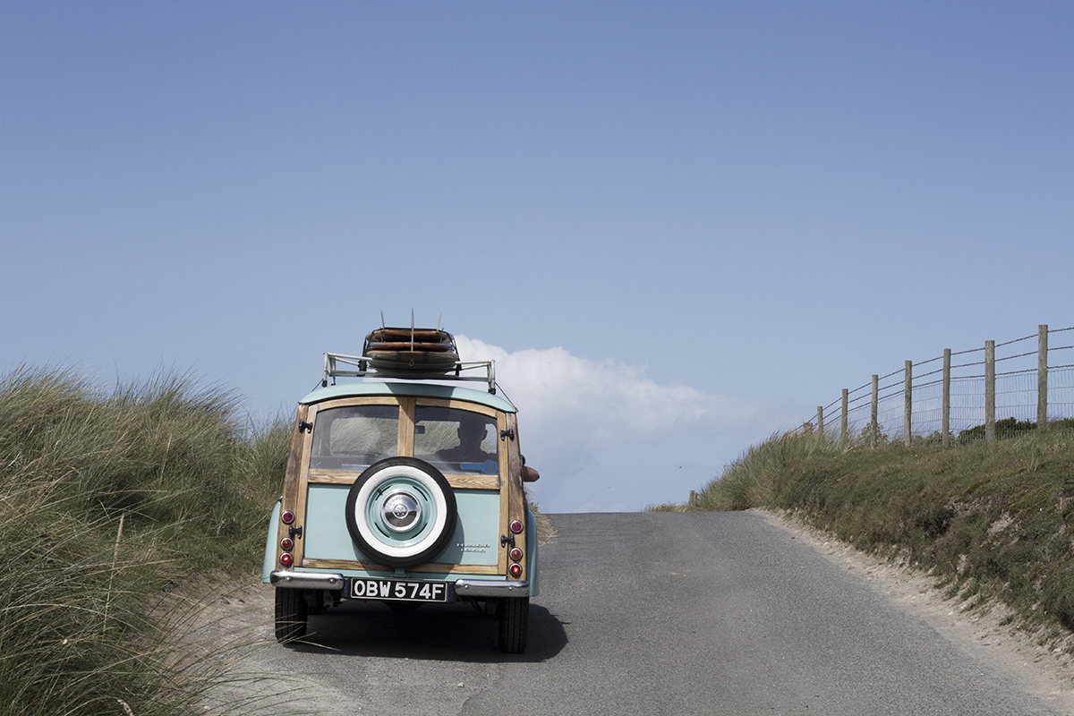 morris minor with otter wooden surfboards on roof driving over brow of hill in sand dunes