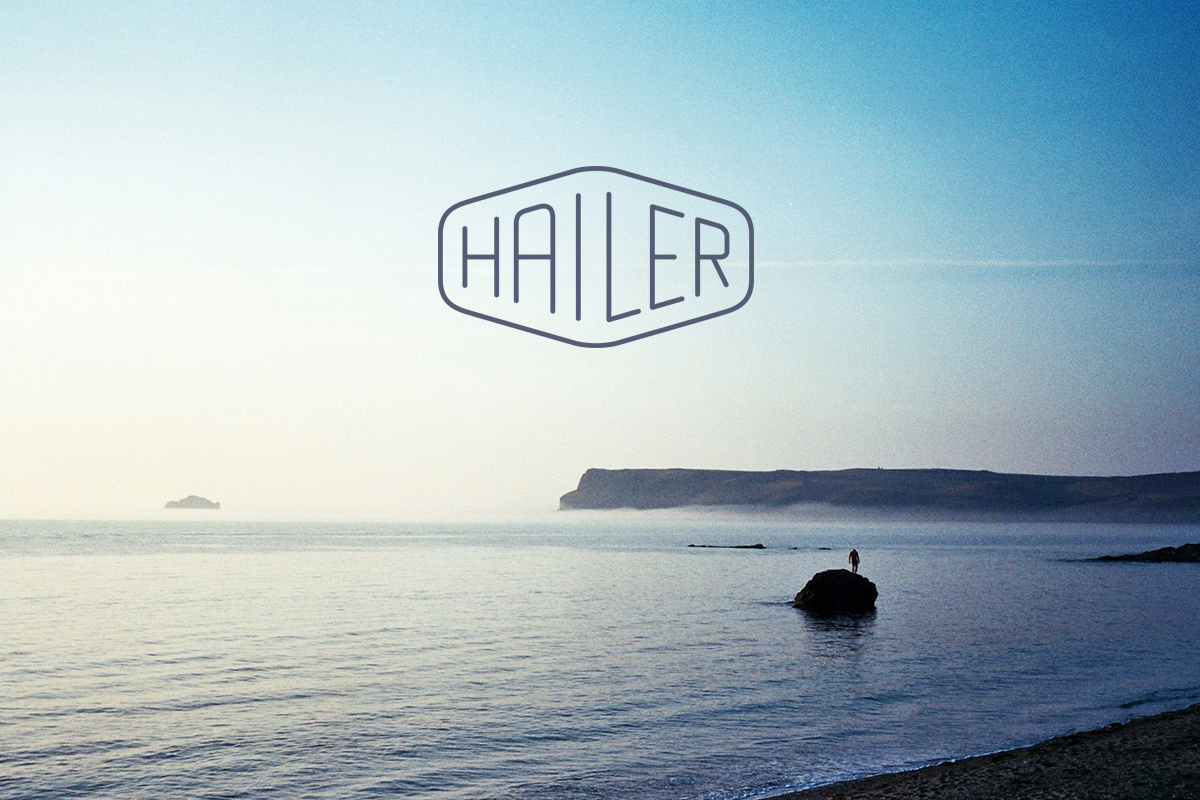 hailer logo overlaid on photo of pentire point on a summer evening with a man stood on a rock in the sea