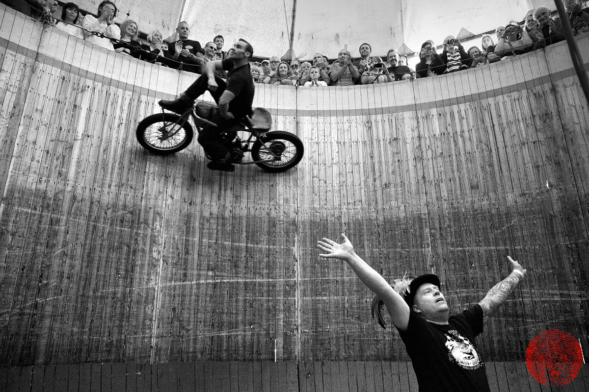 the duke riding a vintage indian motorcycle sat on the handlebars on the demon drome wall of death with the compere beneath him
