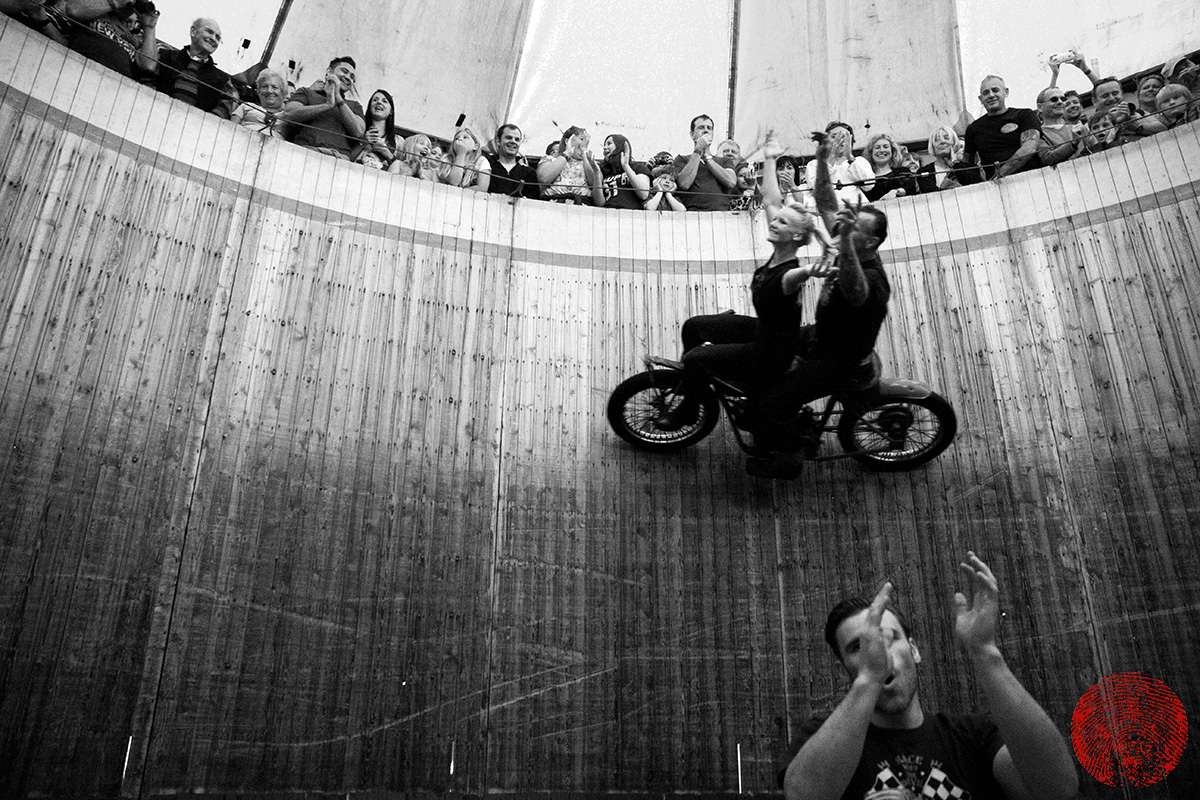 dynomyte dave seymour and his daughter alabama riding a vintage indian motorcycle hands free on the demon drome wall of death with the duke applauding at the bottom
