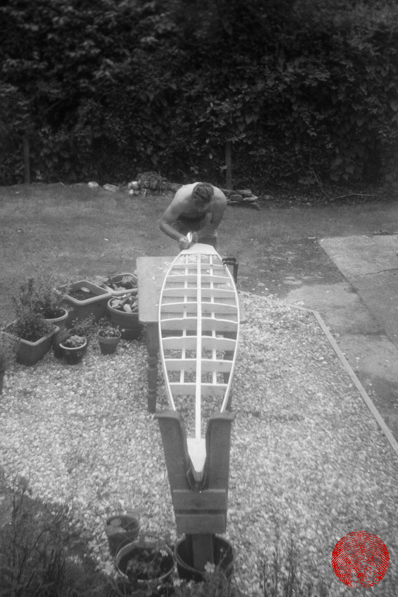 black and white image of harry knight building the framework for a wooden cigar box surf board