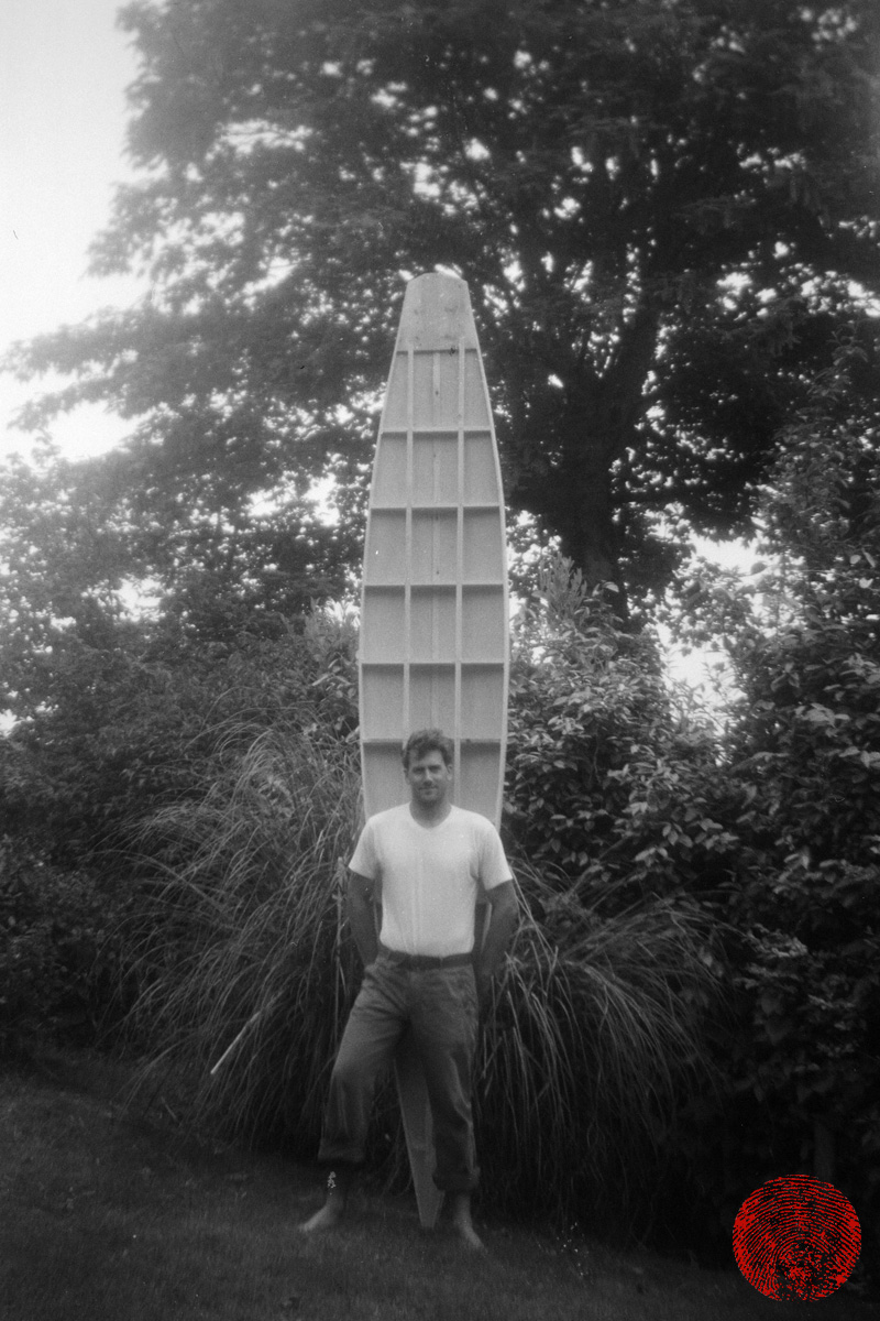 surfer harry knight posing in front of a replica 1920s tom blake style wooden cigar box surfboard, photographed with a kodak box brownie
