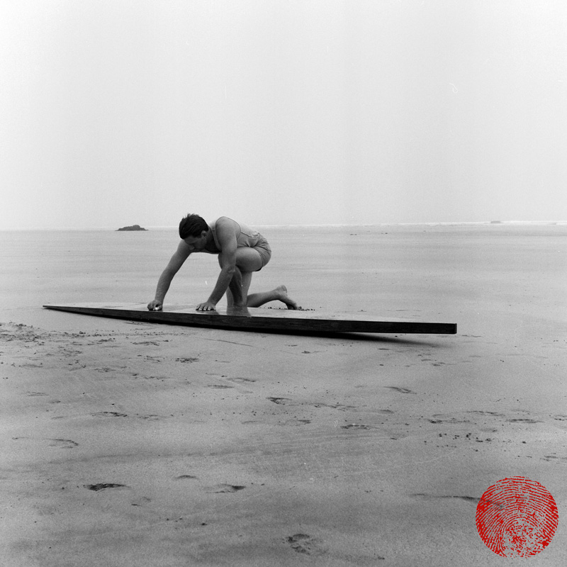 black and white image of a surfer wearing heritage shorts waxing a wooden surfboard on the beach