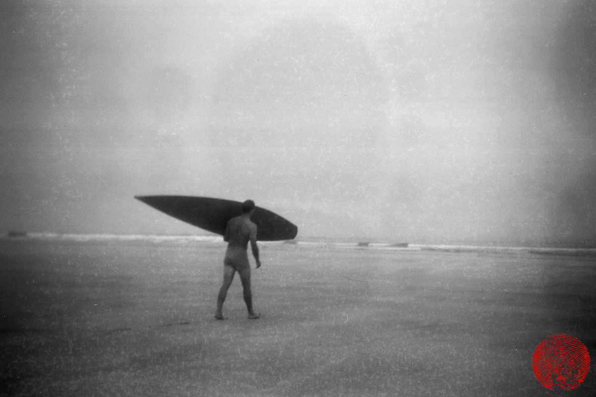 black and white image shot using a kodak box brownie of a surfer wearing shorts carrying a wooden tom blake style hollow surfboard towards the ocean