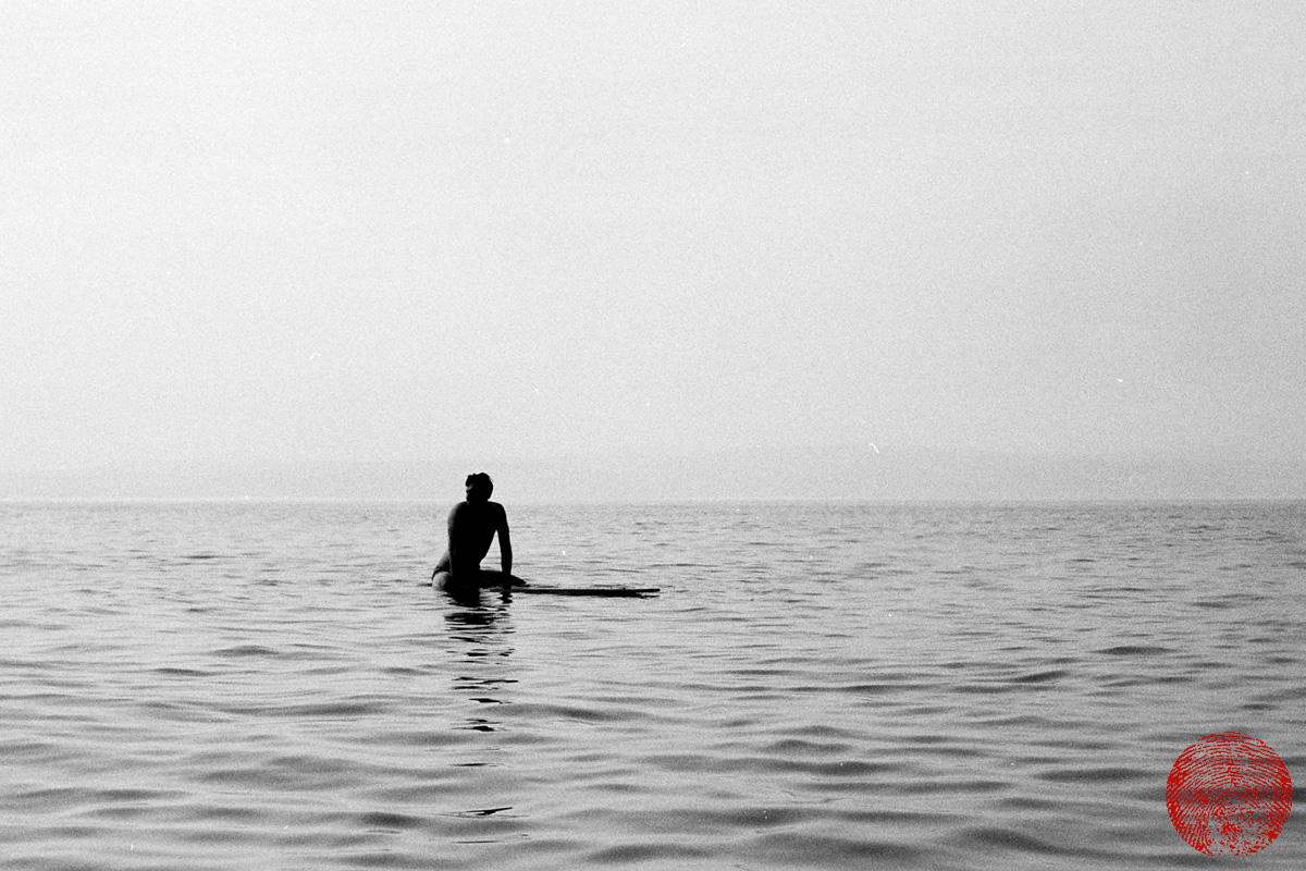 black and white photograph of surfer sitting on a hollow wooden cigar box style surfboard waiting for a wave