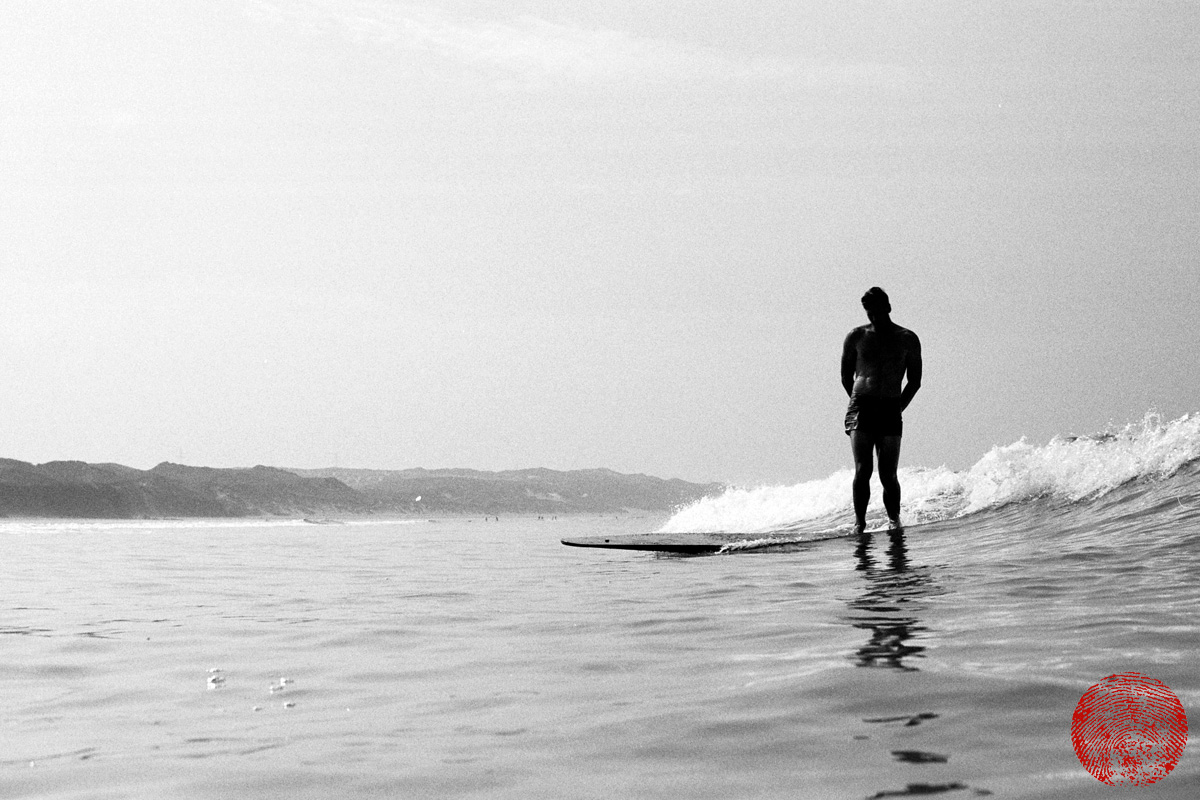 black and white photograph of silhouetted surfer riding a wave on a replica tom blake style hollow wooden surfboard