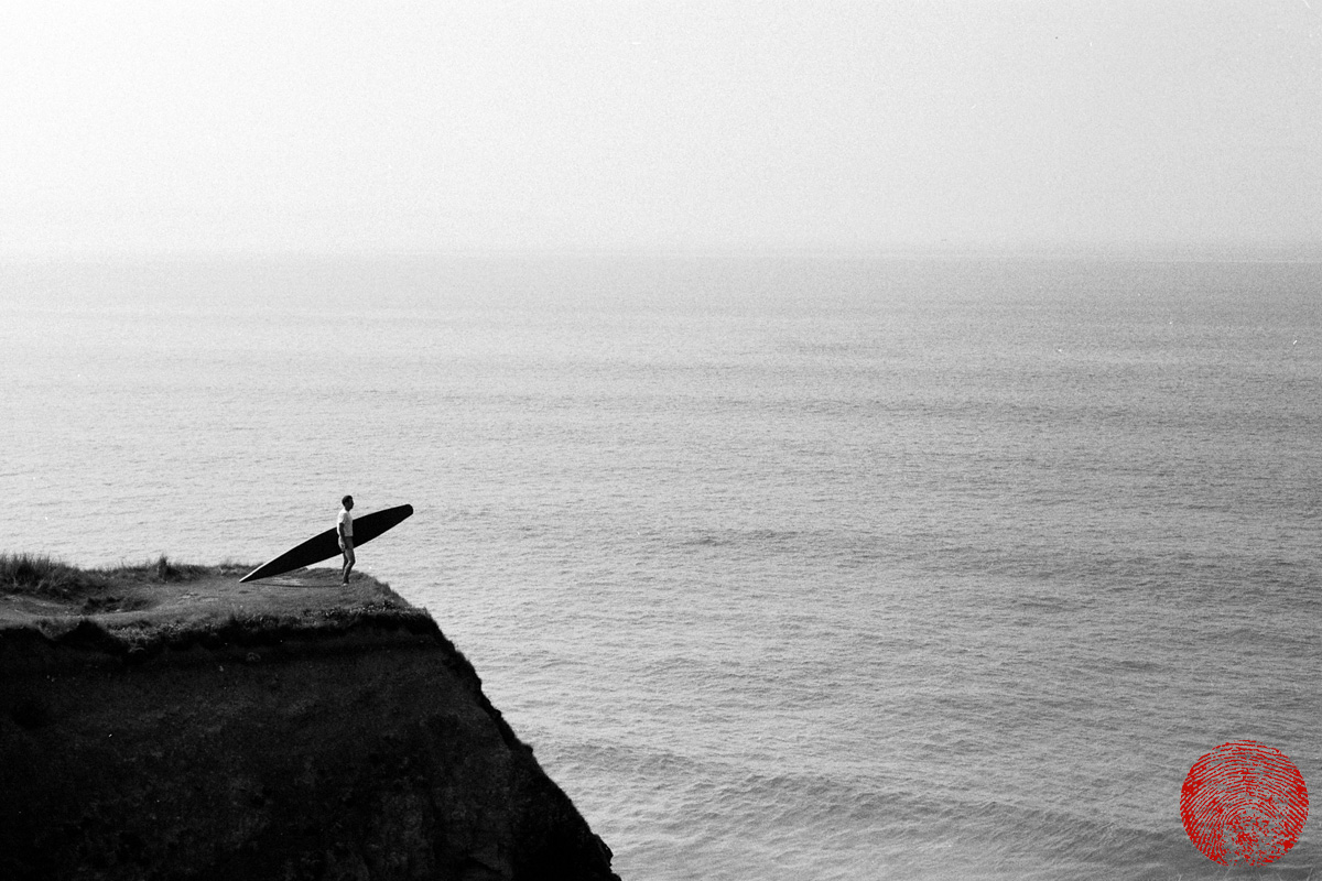 black and white image of a surfer stood on a bluff overlooking the sea holding a replica tom blake style hollow wooden surfboard